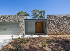 Street view using recycled concrete for texture with zincalume cladding ,recycled timber front door and a skillion roof