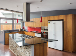 Kitchen with Blackbutt joinery, granite bench and recycled concrete face to living area