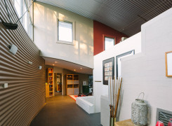 Entry with curved corrugated wall and  stair to studio space