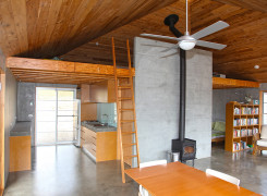 Raked timber ceiling, fan, loft area, kitchen and bedroom with thermal mass floors, walls and chimney wall