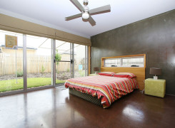 Northern bedroom with ceiling fan and sliding glass doors. Pigmented concrete floors throughout.
